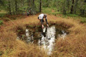 Forfatteren av boka «Sykkeldykk i Finnskog-mystikk, Asbjørn Langmyr, har med mystikk langs skogsveien i Finnskogen passet på å fylle opp vannflaska i «Trollkjelda», i troen på at vannet herfra gir kraftig sisu. Foto: Asbjørn Langmyr
