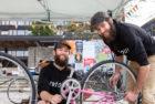 To smilende, skjeggete menn mekker på en rosa sykkel.
