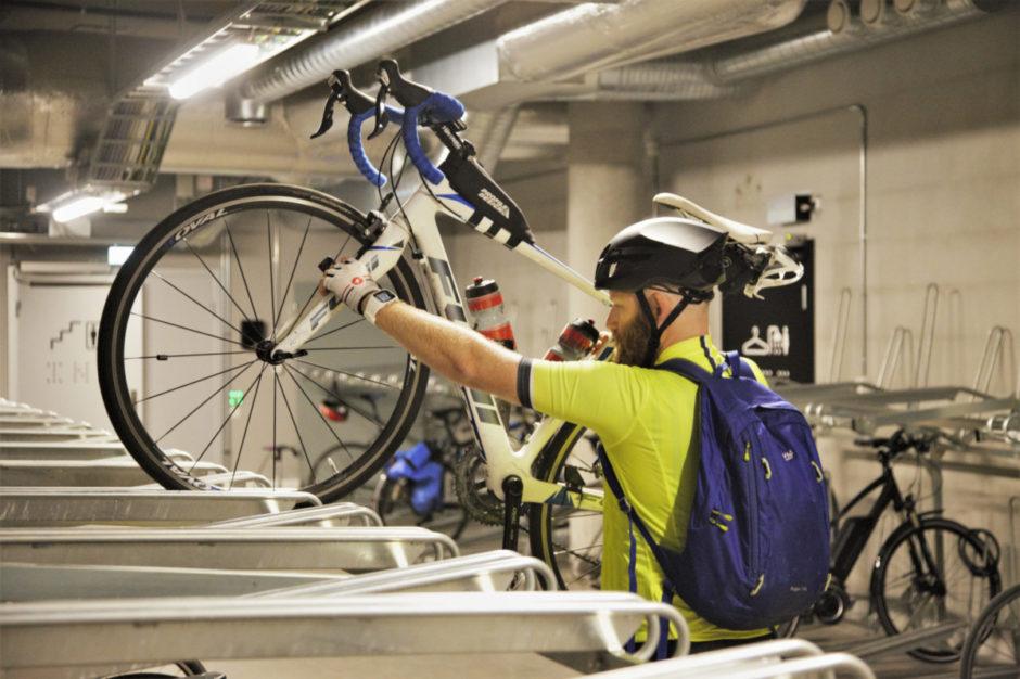 Mann parkerer sykkel i sykkelkjeller