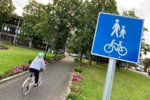 En syklist på en gang- og sykkelvei, blomster og gress på sidene, trær i bakgrunnen, blått skilt i forgrunnen